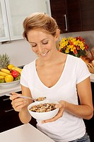 Woman In Kitchen Eating Bowl Of Muesli