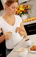 Woman In Kitchen Pouring Tea