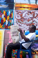 Painting salesman reading newspaper in front of stall near Puerto Plata, Dominican Republic