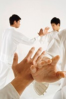 Young men practicing Tai Chi, hands in foreground
