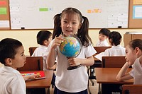 Girl holding globe in classroom, smiling at camera