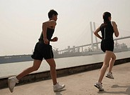 Couple jogging in city, Nanpu bridge in the background