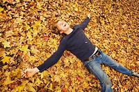 Man laying in autumn leaves