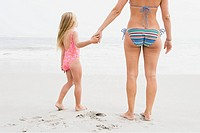 Girl and mother holding hands on beach