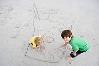 Boys drawing in sand