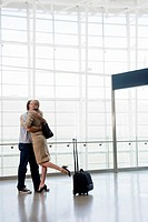 Couple hugging next to suitcase