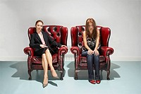 Businesswoman and disheveled woman in comfy leather chairs