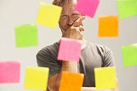 Man looking at a window with colored PostIt Notes