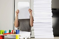 Young woman working from home with huge pile of paper