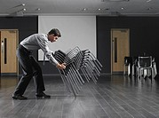 Man moving stack of chairs in empty presentation room