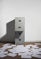 Filing cabinet against wall with papers strewn about