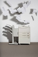 A photocopier against a white wall with paper flying out