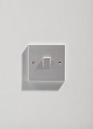 Electrical light switch on white wall