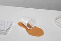 A plastic cup lies in a pool of spilt tea on a desk