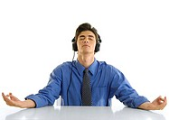Close-up of a businessman practicing yoga and listening to music