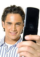 Close-up of a young man text messaging with a mobile phone and smiling