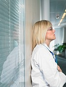 Pensive female doctor leaned on glass wall in a lobby of a hospital close up