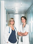 Two female doctors looking at camera in a lobby of a hospital smiling Portrait