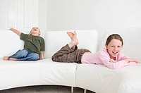 Children relaxing on sofa