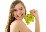 Portrait of a young woman holding a bunch of grapes and grining