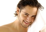Portrait of a young man wiping his hair with a towel