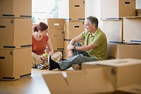 Couple relaxing among cardboard boxes
