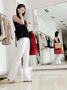 Woman using cell phone in clothes store