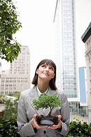 Businesswoman holding bonsai tree