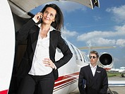 Businesswoman outside of jet in front of pilot