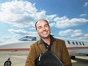 Smiling man standing next to private jet