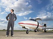 Technician in gray overall standing in front of private jet on tarmac