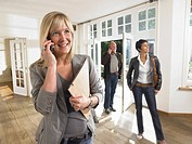 Female real estate agent on phone in show house clients behind