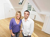 Couple standing in empty loft