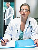 Portrait of female doctor at her desk with male doctor in background