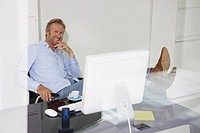 Man at computer smiling relaxing with feet on desk with reflections