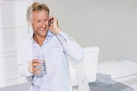 Smiling man in office on phone