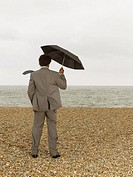 Businessman with Umbrella on Beach