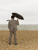 Businessman with Umbrella on Beach