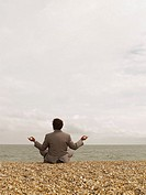 Businessman in Yoga Position on Beach