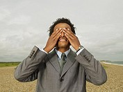 Businessman Covering Eyes on Beach