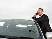 Businessman Leaning Against Car on Cell Phone