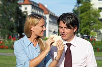 Businesswoman feeding sandwich to businessman