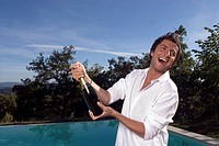 Man opening a bottle of champagne by a pool