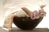 Massage belt and heart-shaped soap decorated with flowers in a wooden bowl