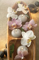 Arrangement of candles and orchid blossoms in a wooden bowl