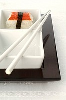 Sushi in a small bowl with chopsticks