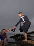 Businesswoman on a dock passing man her shoes