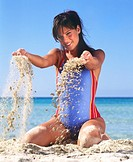 Woman in swimsuit playing with sand (thumbnail)