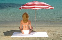 Woman sitting on the beach under a sunshade - back view