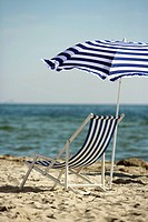 Blue and white sunshade and deckchair on the beach
